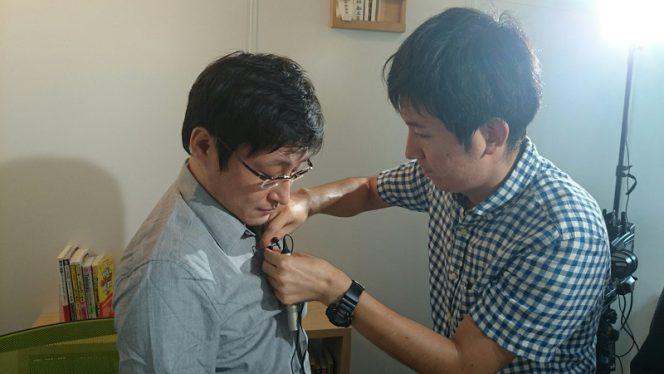 ピンマイクをつける坂本さん